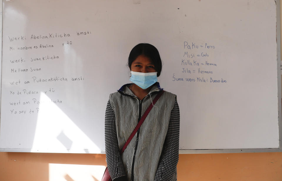 """Abelina Choque stands inside her classroom next to her work, left, she wrote out on a dry erase board, during an Uru language lesson, in the Urus del Lago Poopo indigenous community, in Punaca, Bolivia, Monday, May 24, 2021. """"The instructors teach us the language with numbers, songs and greetings,"""" said Choque, a 21-year-old student who said she one day would like to teach mathematics. """"It's a little difficult to pronounce."""" (AP Photo/Juan Karita)"""