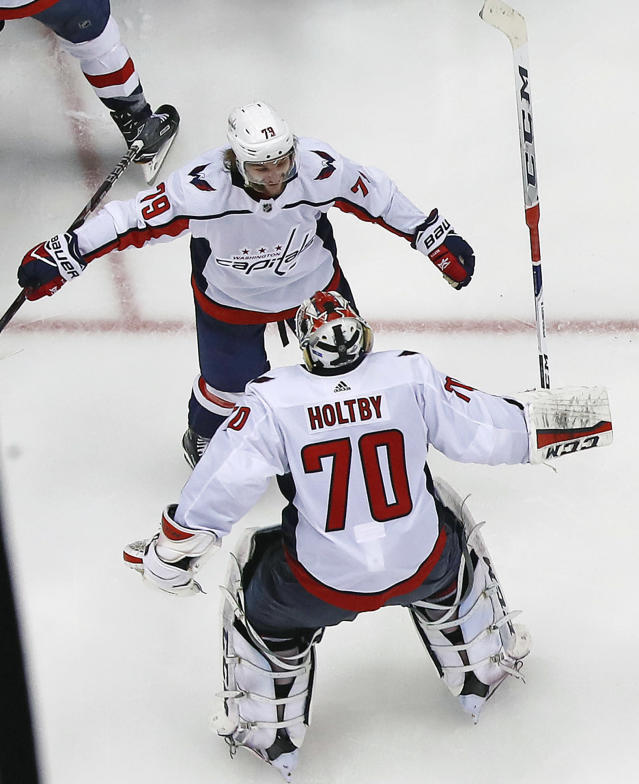 Washington Capitals goaltender Braden Holtby (70) joins the celebration with a hug from Nathan Walker (79) after Evgeny Kuznetsovs' game-winning goal during the overtime period in Game 6 of an NHL second-round hockey playoff series against the Pittsburgh Penguins in Pittsburgh, Monday, May 7, 2018. The Capitals won the game 2-1 to take the series, four games to two. AP Photo/Gene J. Puskar)
