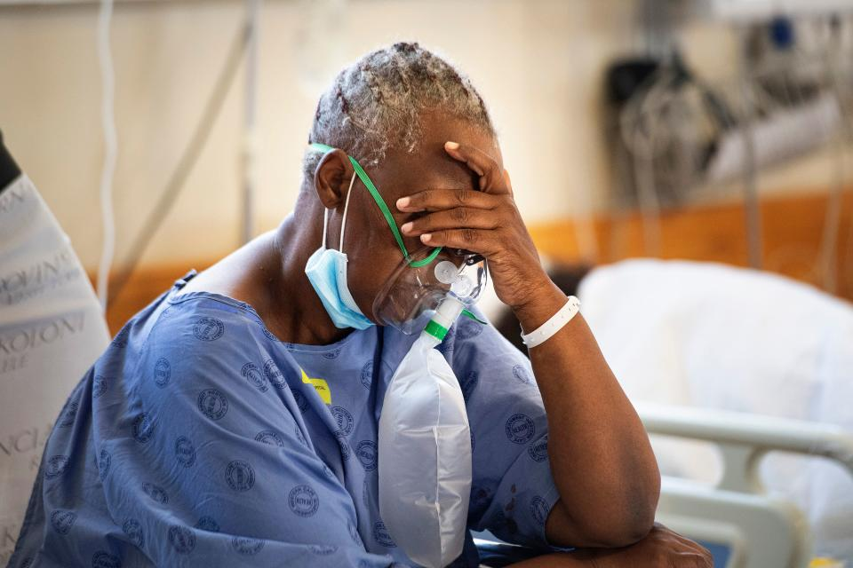 TOPSHOT - A patient with the COVID-19 breaths in oxygen in the COVID-19 ward at Khayelitsha Hospital, about 35km from the centre of Cape Town, on December 29, 2020. - The patents in this ward are not critically serious, but do require oxygen and to lie down.  South Africa has become the first African nation to record one million coronavirus cases, according to new data published by the country's health ministry on December 27, 2020.  Currently suffering a second wave of infections, of which the majority are a new variant of the coronavirus, South Africa is the hardest hit country on the African continent. (Photo by RODGER BOSCH / AFP) (Photo by RODGER BOSCH/AFP via Getty Images)