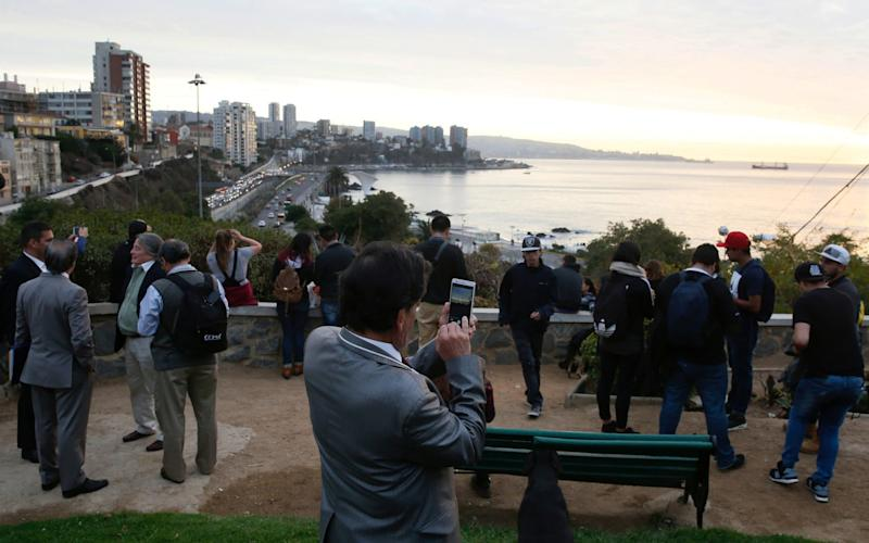 People stand and watch the ocean in Chile before the threat of a tsunami after the 7.1 quake passed - Credit: Reuters