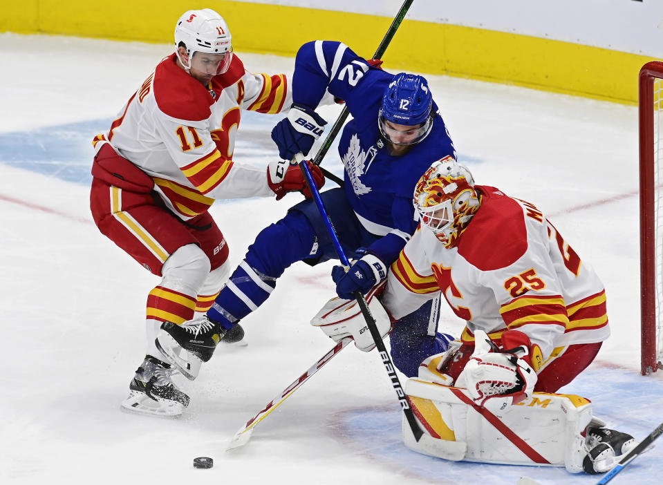 Calgary Flames goaltender Jacob Markstrom (25) makes a save as Flames' Mikael Backlund (11) and Toronto Maple Leafs' Alex Galchenyuk (12) look for a rebound during the second period of an NHL hockey game Tuesday, April 13, 2021 in Toronto. (Frank Gunn/Canadian Press via AP)