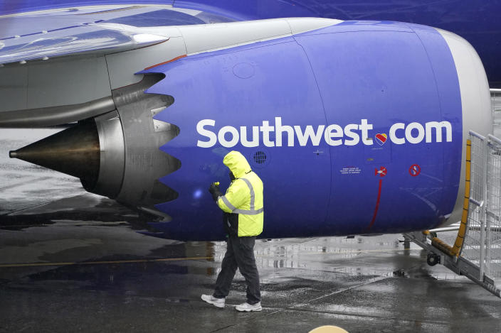 A worker uses a flashlight to inspect an engine on a Boeing 737 Max 8 built for Southwest Airlines at Renton Municipal Airport, Wednesday, Nov. 18, 2020, in Renton, Wash. After nearly two years and a pair of deadly crashes, the U.S. Federal Aviation Administration announced Wednesday that the 737 Max has been cleared for flight after regulators around the world grounded the Max in March 2019, after the crash of an Ethiopian Airlines jet. (AP Photo/Ted S. Warren)