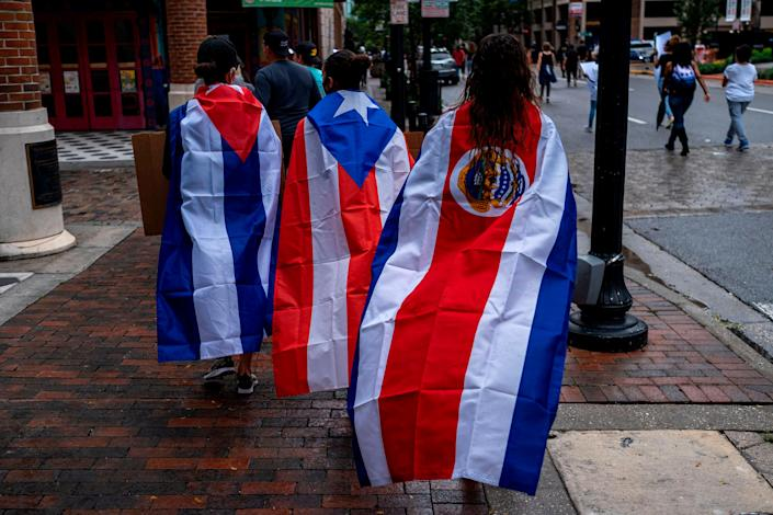 "Protesters wear Cuban, Puerto Rican and Costa Rican flags during an anti-racist protest in Orlando, Florida, after the killing of George Floyd this spring. While Trump has accused Joe Biden of favoring radical ""socialism"" and fomenting unrest, the Biden campaign has begun to compare Trump's response to the protests to the authoritarian tendencies of the Latin American leaders the U.S. president claims to oppose. (Photo: RICARDO ARDUENGO via Getty Images)"