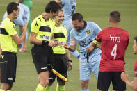 Player Idan Vered, right, checks the fingernails of referee Sapir Berman, center left, during an Israeli Premier League soccer match between Hapoel Haifa and Beitar Jerusalem in the northern Israeli city of Haifa, Monday, May 3,2021. Israeli soccer's first transgender soccer referee took the field Monday for the first time since coming out publicly as a woman last week. (AP Photo/Sebastian Scheiner)