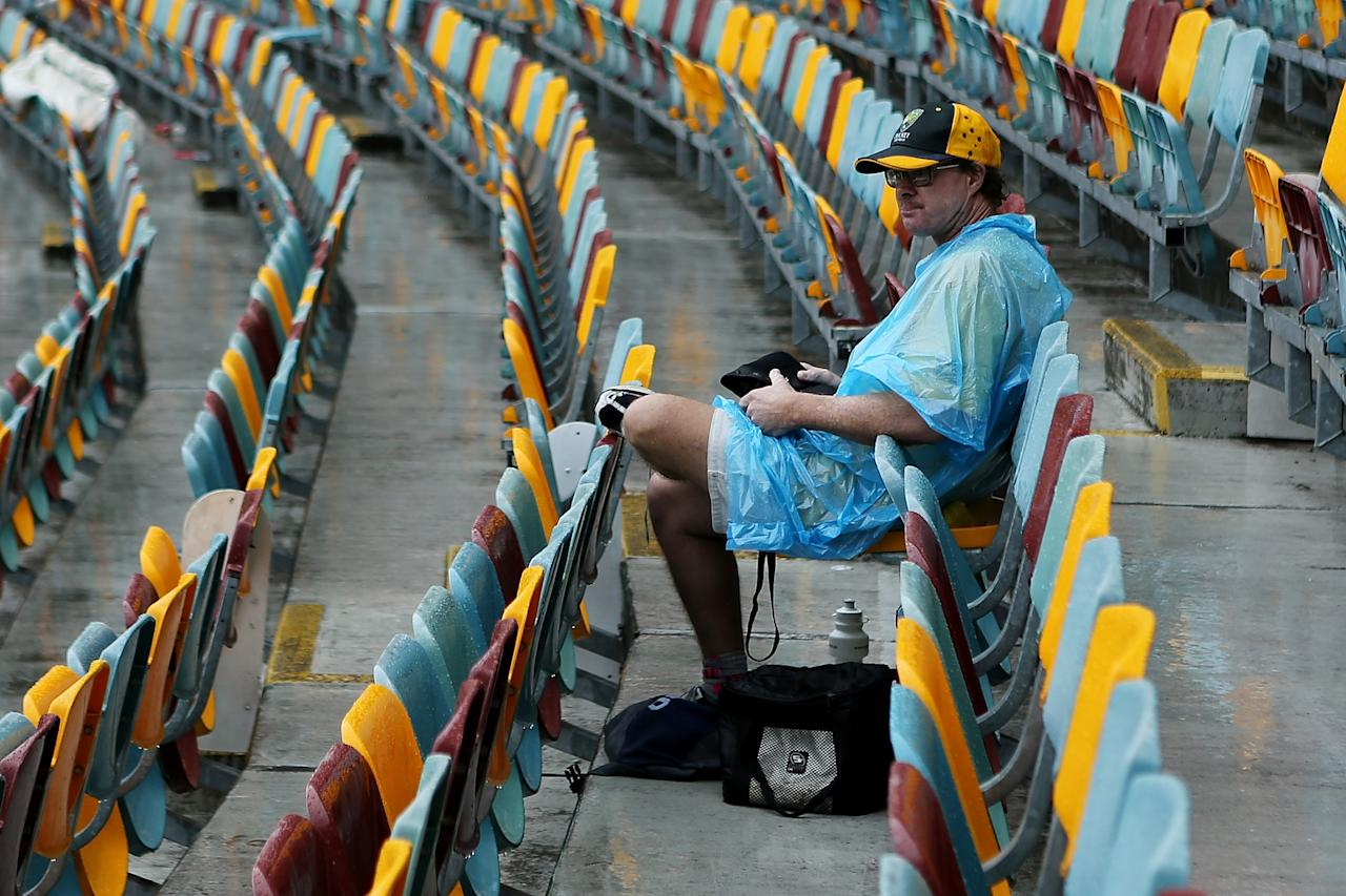 BRISBANE, AUSTRALIA - NOVEMBER 10:  A spectator sits in the stands as rain continues to delay play on day two of the First Test match between Australia and South Africa at The Gabba on November 10, 2012 in Brisbane, Australia.  (Photo by Chris Hyde/Getty Images)