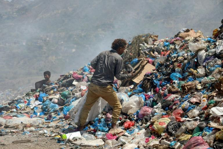 Youths salvage items from a garbage dump in the city of Taez in southwestern Yemen