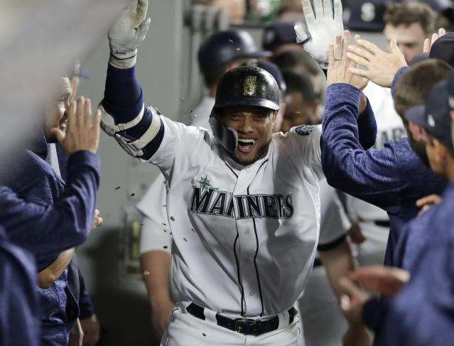 Sunflower seeds fly as Seattle Mariners' Robinson Cano is greeted in the dugout after he hit a solo home run against the San Diego Padres during the third inning of a baseball game, Tuesday, Sept. 11, 2018, in Seattle. (AP Photo/Ted S. Warren)