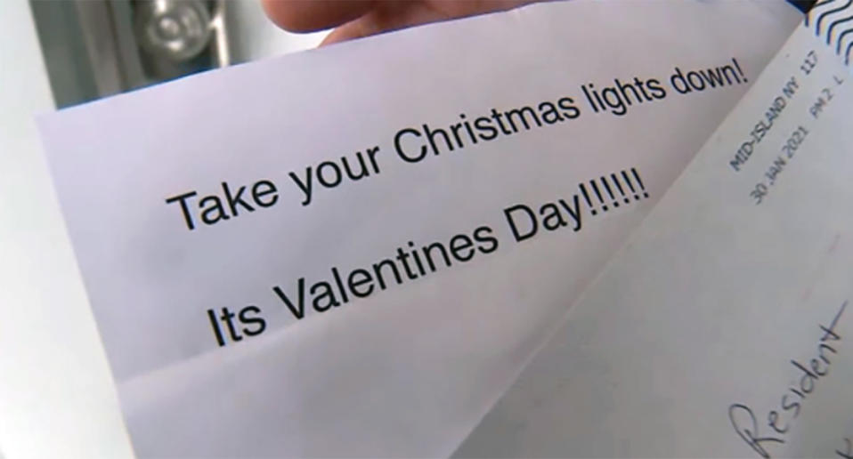 A printed letter says: Take your Christmas lights down! It's Valentine's Day!!!