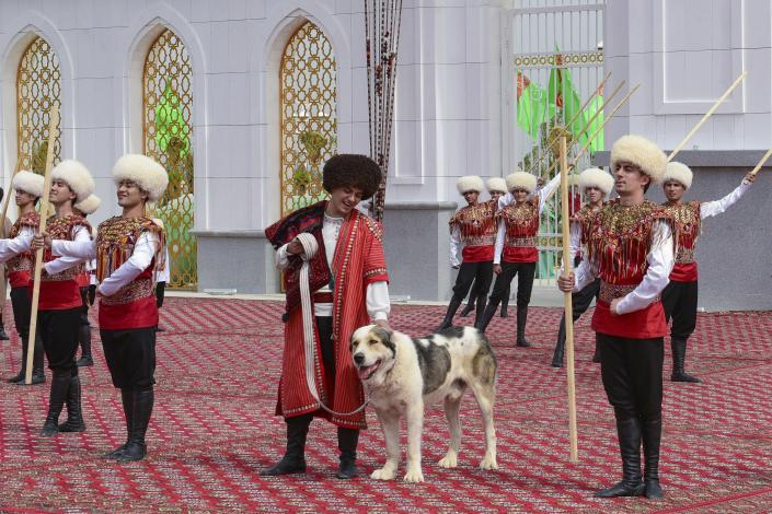 A man dressed in a national costume, center, pets his border guard shepherd dog Alabay during Dog Day celebration in Ashgabat, Turkmenistan, Sunday, April 25, 2021. The Central Asian nation of Turkmenistan has celebrated its new state holiday honoring the native Alabay dog breed. President Gurbanguly Berdymukhamedov established the holiday to be observed on the same day that Turkmenistan lauds its Akhla-Teke horse, a breed known for its speed and endurance. (AP Photo)