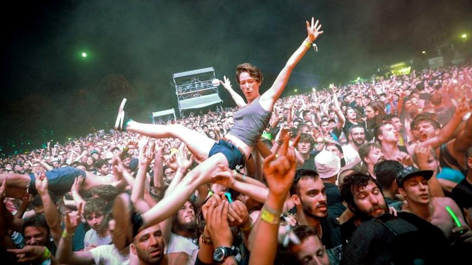 A fan crowd-surfs at a rock concert