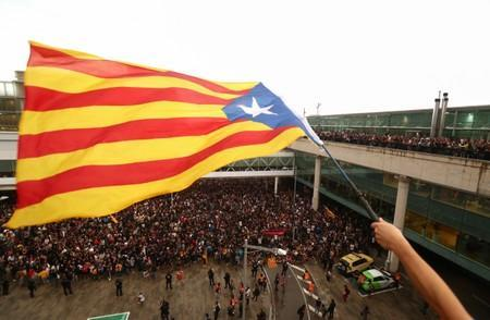 A protester waves an Estelada (Catalan separatist flag) during a demonstration outside the airport in Barcelona