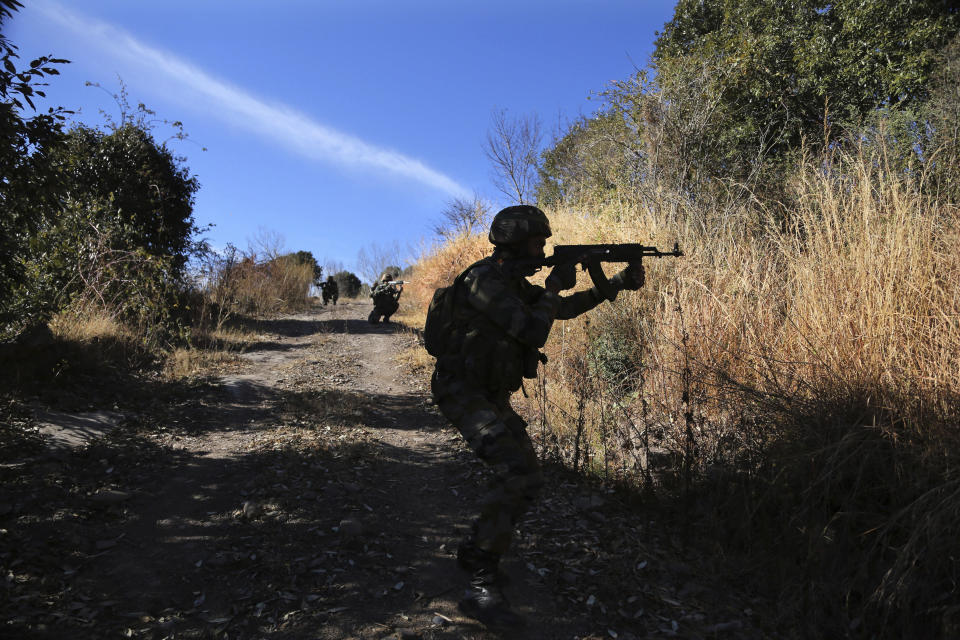 Indian army soldiers display their way of patrolling along the Line of Control, that divides the region between India and Pakistan, during a media trip to their area in Balakot in Poonch, about 250 kilometers (156 miles) from Jammu, India, Friday, Dec. 18, 2020. AP journalists were recently allowed to cover Indian army counterinsurgency drills in Poonch and Rajouri districts along the Line of Control. The training focused on tactical exercises, battle drills, firing practice, counterinsurgency operations and acclimatization of soldiers to the harsh weather conditions. (AP Photo/Channi Anand)