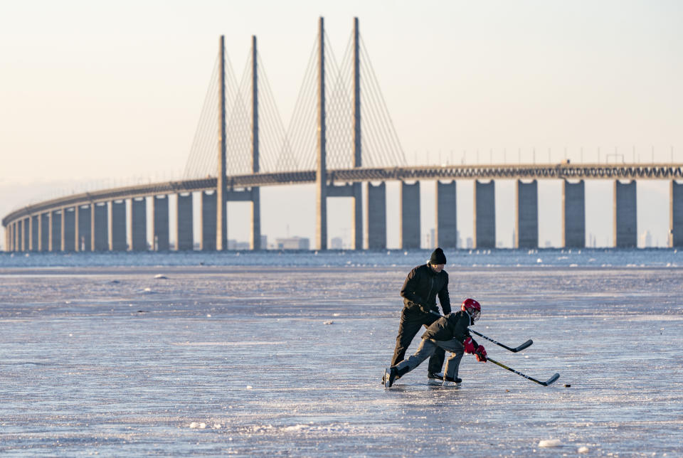 Skaters play hockey on the ice that settled on the Oresund strait, Wednesday Feb, 10, 2021, at Bunkeflostrand a suburb of Malmo, Sweden, south of the Oresund Bridge. (Johan Nilsson/TT via AP)