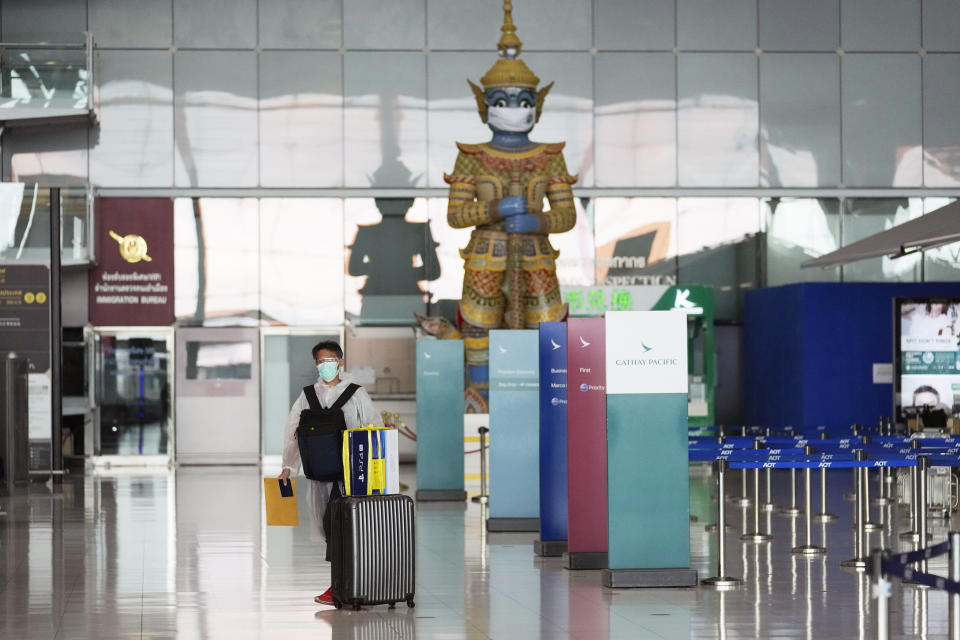 A lone passenger wearing a face mask to help curb the spread of the coronavirus stands with his luggage at the Suvarnabhumi airport in Bangkok, Thailand, Wednesday, July 21, 2021. The Civil Aviation Authority of Thailand has ordered a halt to all domestic flights operating from the most severely affected provinces effective Wednesday. Exceptions are allowed for flights to destinations that are part of a plan that allows vaccinated travelers from abroad to stay for two weeks on popular islands such as Phuket and Samui without quarantine confinement. (AP Photo/Sakchai Lalit)