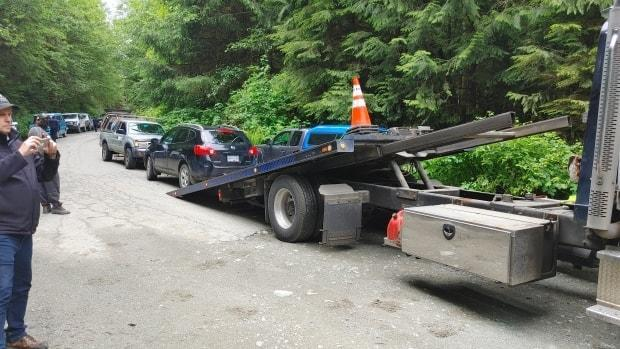 A car on the side of the logging road is seen being towed in the Fairy Creek logging zone on June 6, 2021. Protesters are suing the logging company for charging them over $2,500 to retrieve their vehicles. (Submitted by Carole Tootill - image credit)