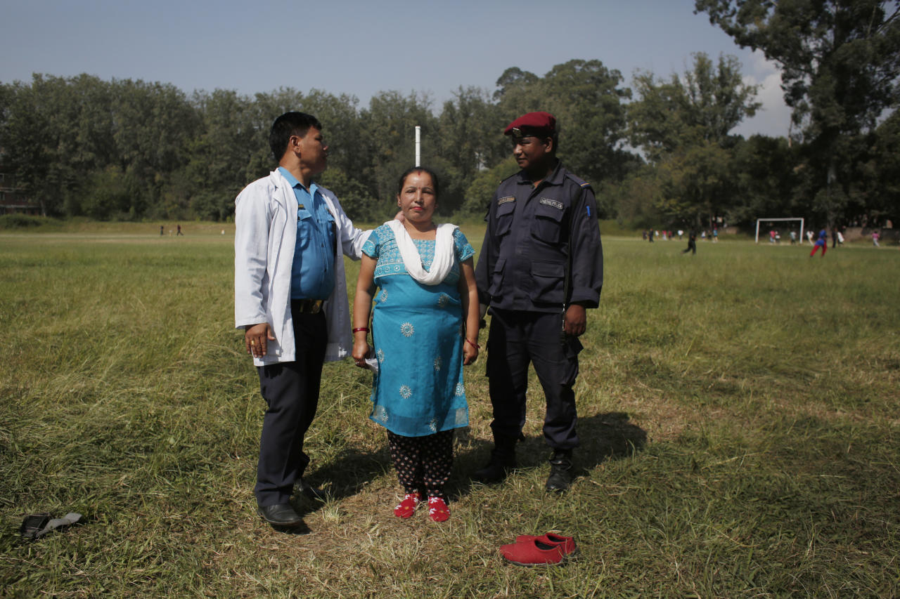 In this Oct. 24, 2017, photo, Nepalese policemen measure the height of a woman during a physical fitness test to recruit temporary policemen for the upcoming legislative election in Kathmandu, Nepal. Eleven years after Nepal began its journey toward democracy by stripping its authoritarian king of his powers, the nation's 30 million people will finally get a say in running their local regions, giving voice to those who feel overlooked in a country with diverse ethnic groups and cultures. (AP Photo/Niranjan Shrestha)