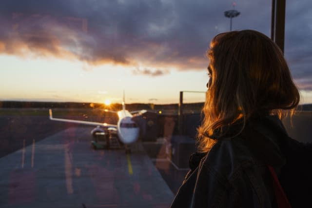 Young woman looking through window on plane at the airport at sunset