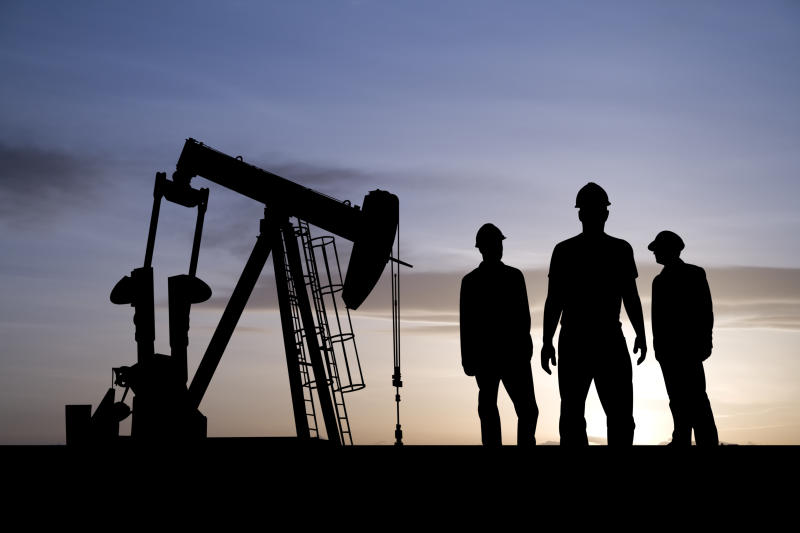 Three men who work in the oil and gas field have a meeting as a pumpjack works behind them.