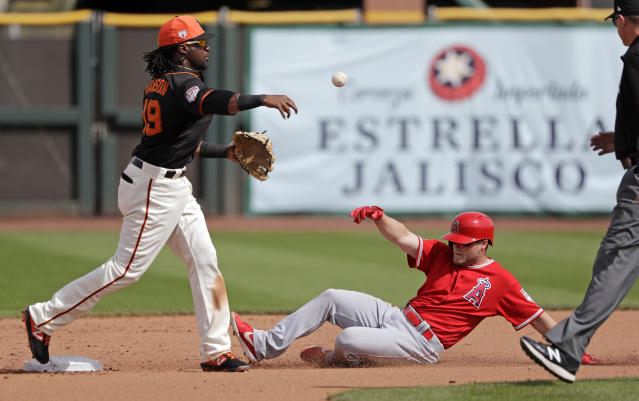 San Francisco Giants shortstop Alen Hanson, left, throws to first base after forcing out Los Angeles Angels' Brennon Lund at second base in the fifth inning of a spring training baseball game Friday, March 15, 2019, in Phoenix. The Angels' Jose Rojas was out at first on the double play. (AP Photo/Elaine Thompson)