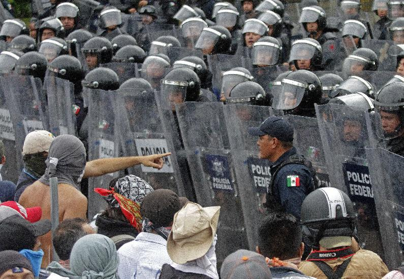 Demonstrators confront riot police during a protest against the suspected massacre of 43 missing Mexican students, near Acapulco's airport on November 10, 2014 (AFP Photo/Pedro Pardo)