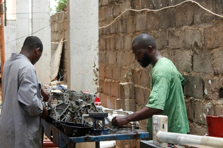 """Mechanic Joao Pande, right, says corruption still permeated all levels of Angolan society. """"If you know someone... they will do what you want and then you pay"""" (AFP Photo/Sofia Christensen)"""