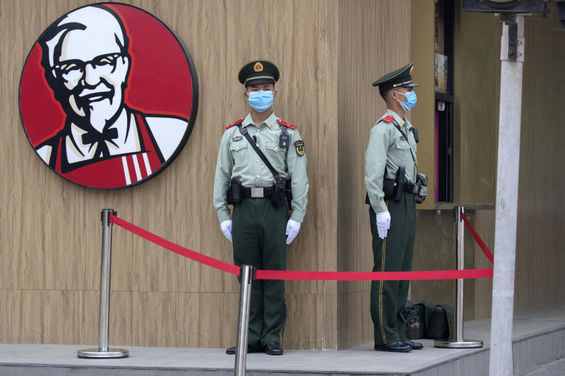 Chinese paramilitary policemen wearing masks to curb the spread of the new coronavirus stand guard near a logo for KFC before the opening session of the Chinese People's Political Consultative Conference (CPPCC) is to be held at the Great Hall of the People in Beijing, Thursday, May 21, 2020. (AP Photo/Ng Han Guan)