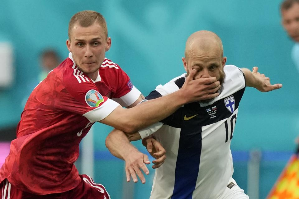 Russia's Dmitri Barinov, left, fouls Finland's Teemu Pukki during the Euro 2020 soccer championship group B match between Russia and Finland at the Saint Petersburg stadium, in St. Petersburg, Russia, Wednesday, June 16, 2021. (AP Photo/Dmitri Lovetsky, Pool)