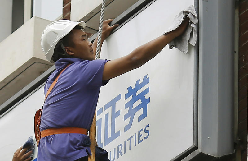A worker cleans the sign of a private securities company Thursday, June 28, 2012, in Shanghai, China. Good news about the U.S. economy helped Asian stock markets rise Thursday, although lingering fears about Europe's ability to tame its debt turmoil kept gains in check.(AP Photo/Eugene Hoshiko)