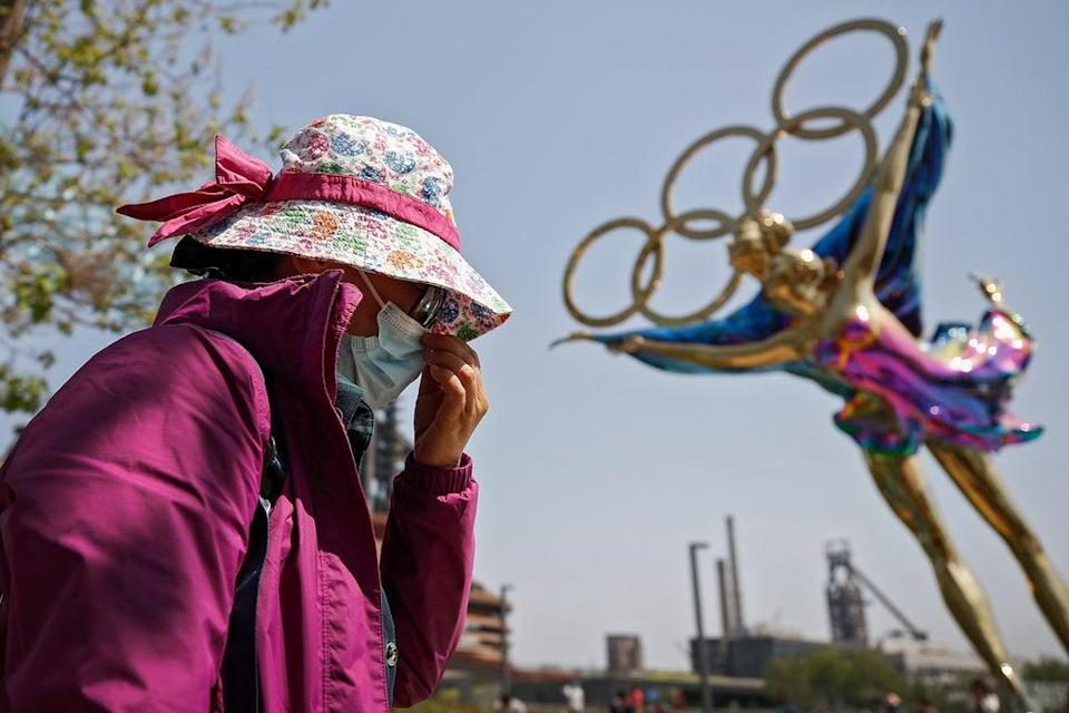 File: A woman adjusts her face mask as she walks by a statue featuring the Beijing Winter Olympics figure (AP)
