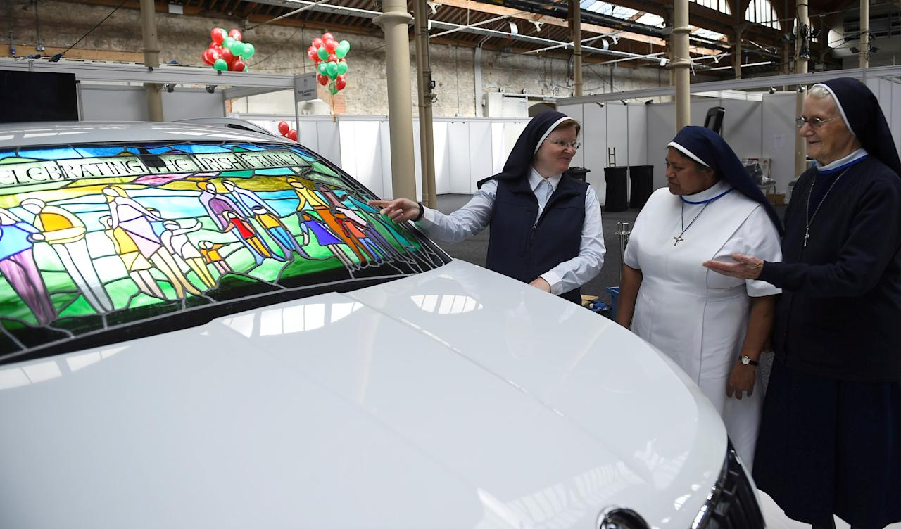 Nuns look at a Skoda car with a stained glass windscreen at the Papal Congress at the World Meeting of Families in Dublin, Ireland August 21, 2018.  REUTERS/Clodagh Kilcoyne      TPX IMAGES OF THE DAY