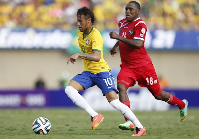 Brazil's Neymar, left, dribbles the ball past Panama's Luis Tejada during a friendly soccer match at the Serra Dourada stadium in Goiania, Brazil, Tuesday, June 3, 2014. Brazil is preparing for the World Cup soccer tournament that starts on 12 June. (AP Photo/Andre Penner)