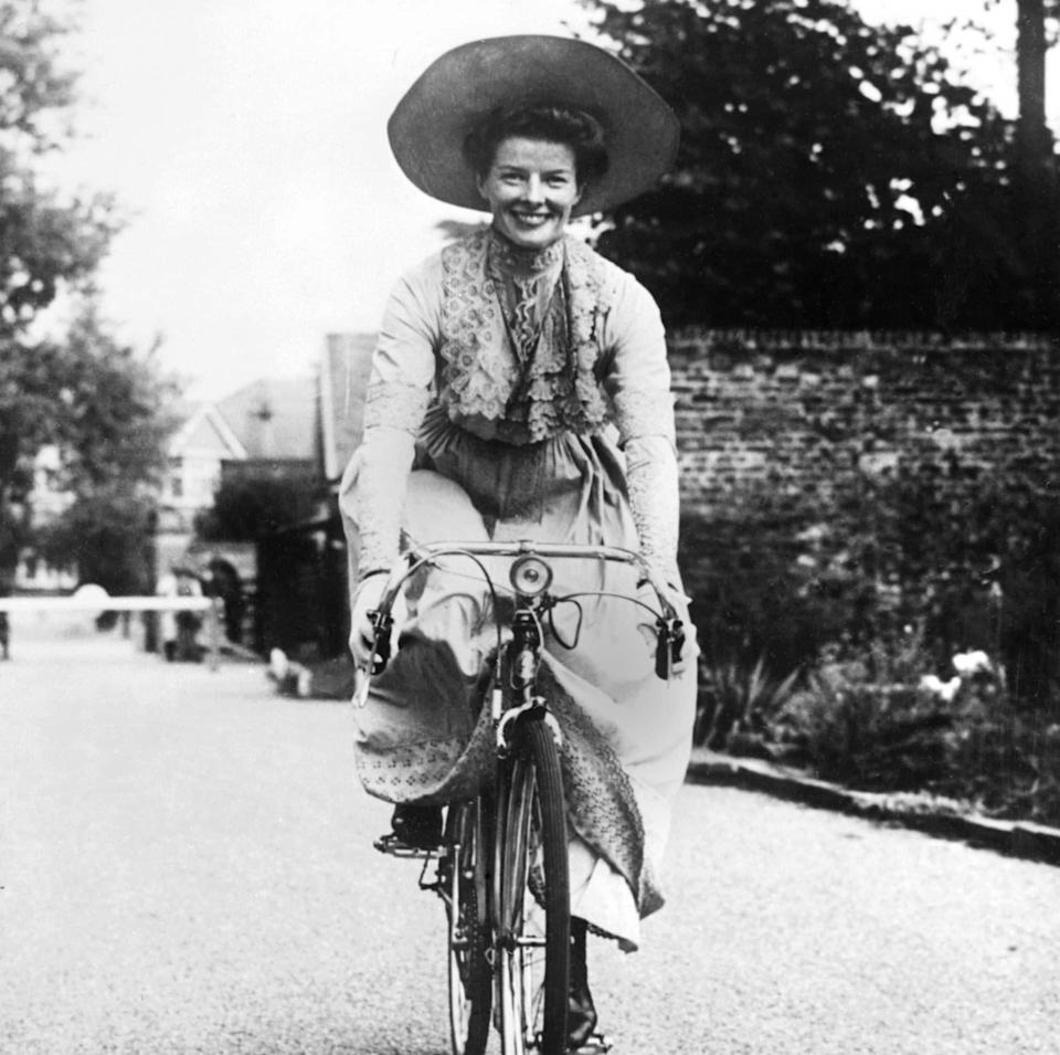 Hepburn rides a bicycle between takes on the set of The African Queen - AFP
