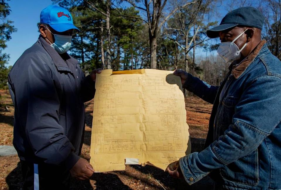 John Goode, left, and Albert Crenshaw hold up a 1938 map of the Oak Grove Cemetery, which was founded by freed African-Americans after the Civil War and now has lost more of its tree buffer to widening of the I-440 Beltline, that separated it from the rest of the Method community in the 1960s, on Wednesday, Feb. 17, 2021, in Raleigh, N.C.