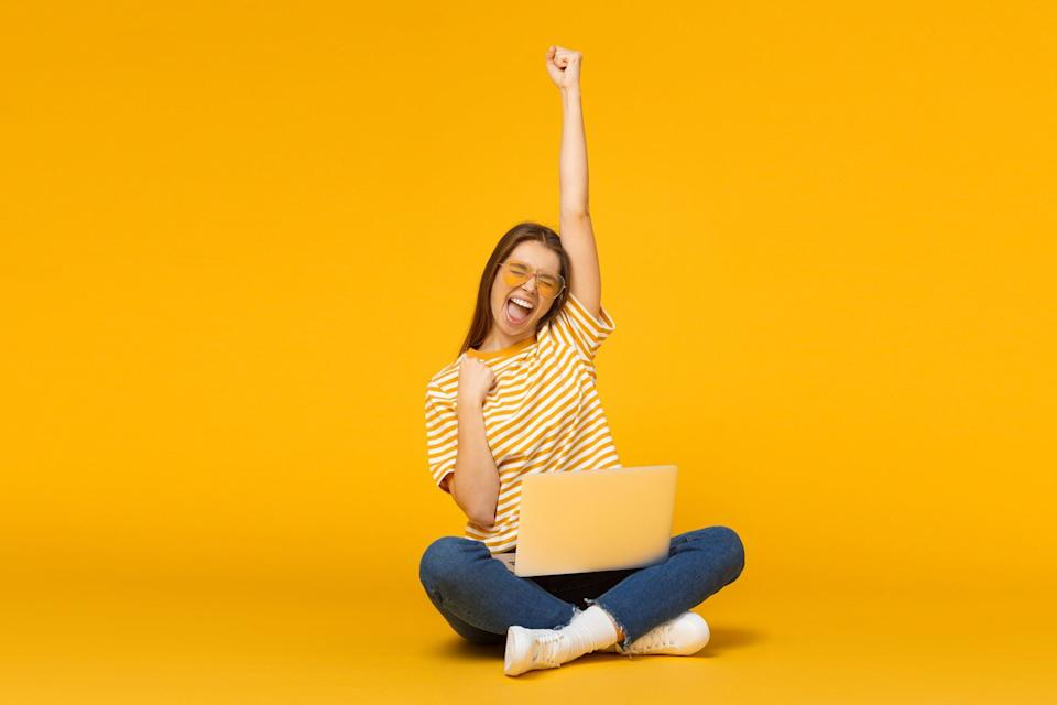 A woman smiling and throwing her hand up.