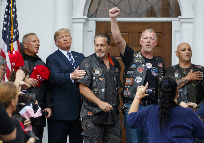 President Donald Trump stands in the rain with members of Bikers for Trump and supporters after saying the Pledge of Allegiance, Saturday, Aug. 11, 2018, at the clubhouse of Trump National Golf Club in Bedminster, N.J. (AP Photo/Carolyn Kaster)