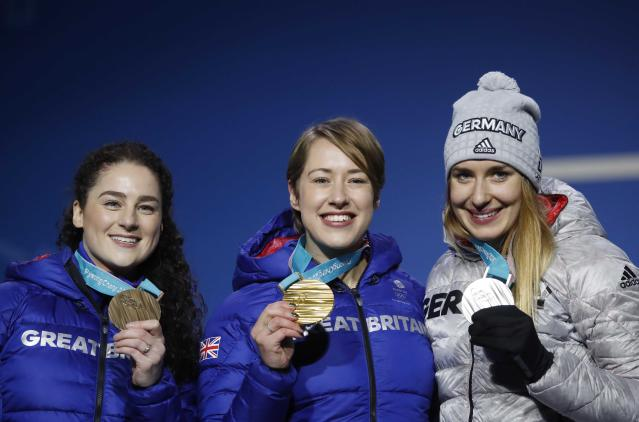 Medals Ceremony - Skeleton - Pyeongchang 2018 Winter Olympics - Women's Skeleton - Medals Plaza - Pyeongchang, South Korea - February 18, 2018 - Gold medalist Lizzy Yarnold of Britain, silver medalist Jacqueline Loelling of Germany and bronze medalist Laura Deas of Britain on the podium. REUTERS/Kim Hong-Ji
