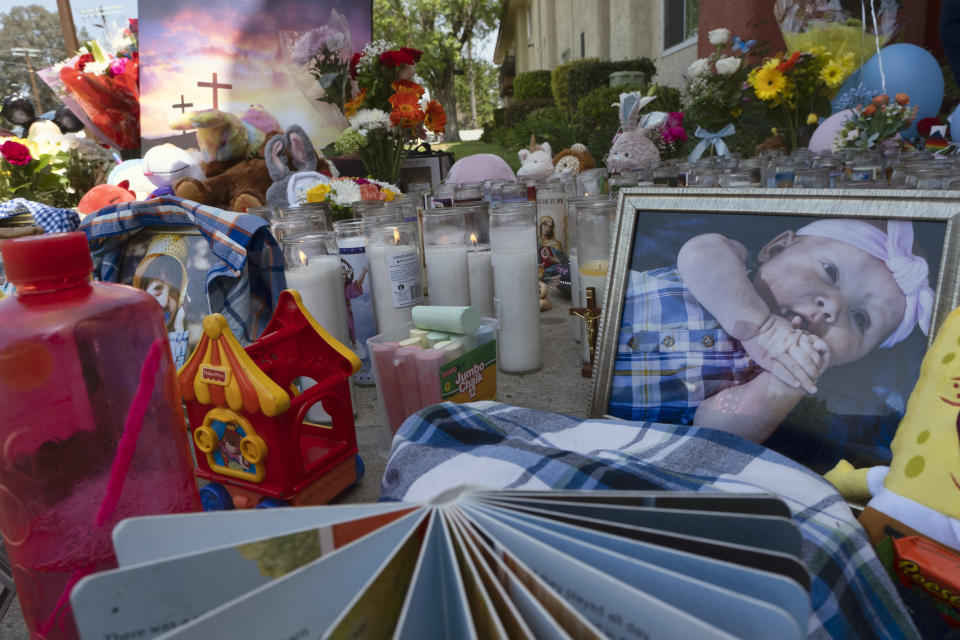 Photos, candles, flowers and balloons are placed as a memorial for three children who were killed at the Royal Villa apartments complex in the Reseda section of Los Angeles
