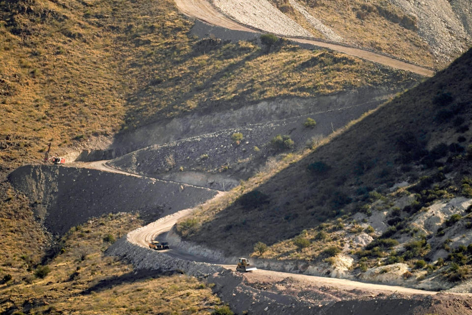 A pathway cleared by explosives to make way for border wall construction separates Mexico, right, and the USA, Wednesday, Dec. 9, 2020, in Guadalupe Canyon, Ariz. Construction of the border wall, mostly in government owned wildlife refuges and Indigenous territory, has led to environmental damage and the scarring of unique desert and mountain landscapes that conservationists fear could be irreversible. (AP Photo/Matt York)