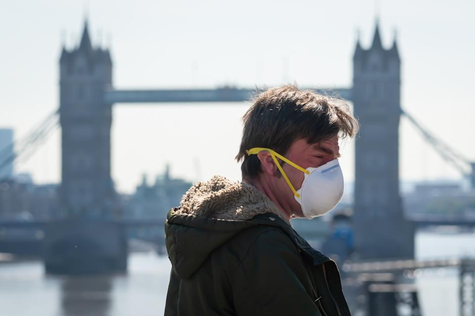 A man wearing a protective face mask crosses London Bridge, in London, during morning rush hour after the introduction of measures to bring the country out of lockdown. (Photo by Dominic Lipinski/PA Images via Getty Images)