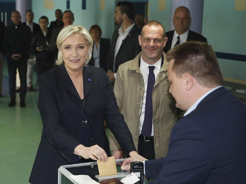 Louis Aliot (c) looks on from behind as presidential candidate and then-Front National leader Marine Le Pen casts her vote in the first round of the election