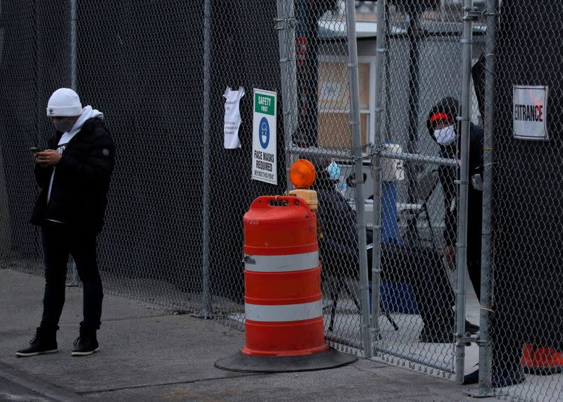 FILE PHOTO: A man uses his phone after being turned away for an appointment at the 24 hour New York State coronavirus disease (COVID-19) mass vaccination site at the Brooklyn Army Terminal, the site was closed after running out of vaccine doses, in Brookly