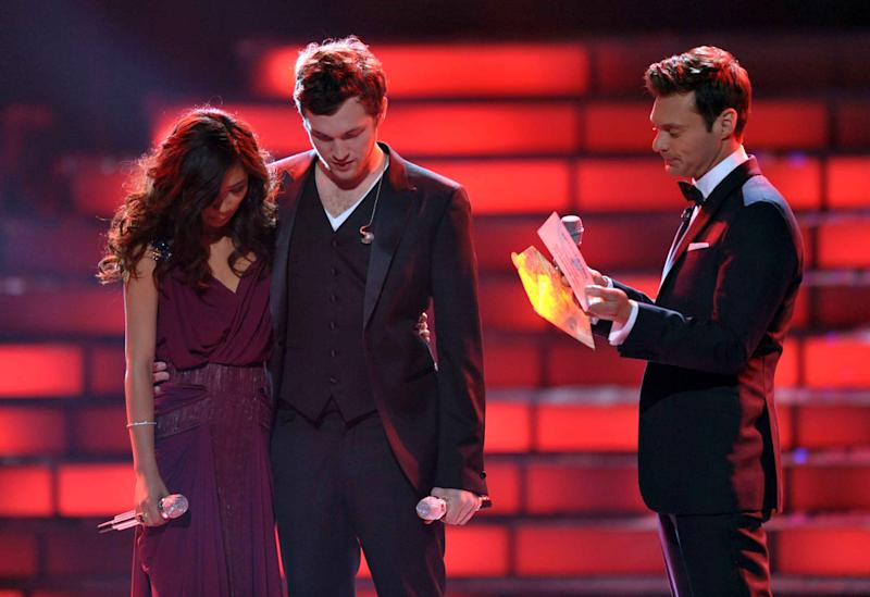 """Finalists Jessica Sanchez, left, and Phillip Phillips, center, listen as host Ryan Seacrest announces the winner onstage at the """"American Idol"""" finale on Wednesday, May 23, 2012 in Los Angeles. (Photo by John Shearer/Invision/AP)"""