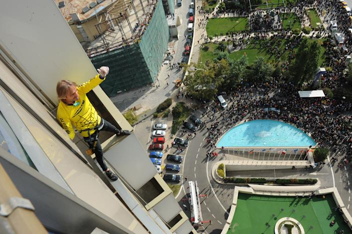 French urban climber Alain Robert, also known as the French Spiderman, celebrates after reaching the top floor of a 22-storey hotel building in Bucharest October 2011. Robert's climb was part of an advertising campaign for a local electronics retailer. (REUTERS/Flanco/Handout)