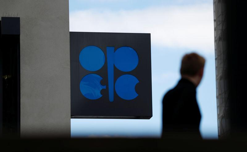 A person passes the OPEC logo in front of OPEC's headquarters in Vienna