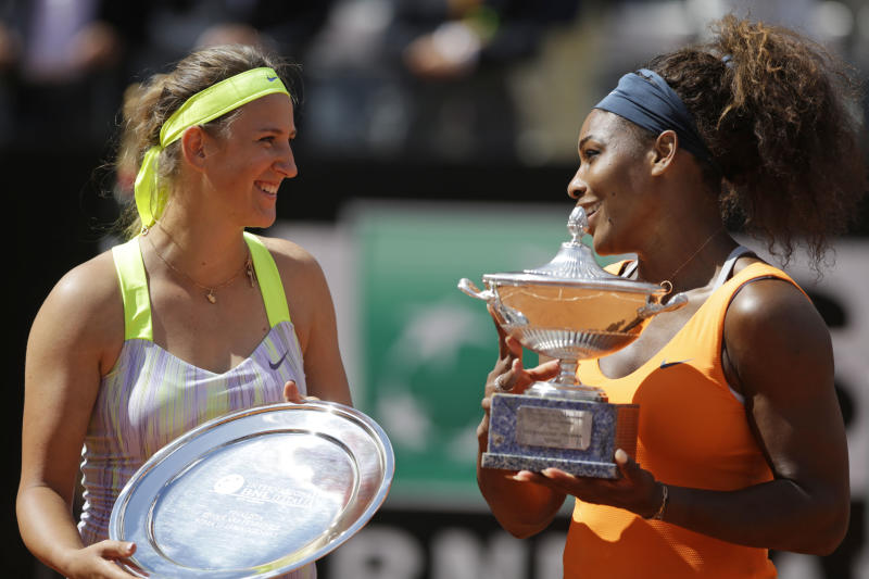 Serena Williams, of the United States, right, flanked by Belarus' Victoria Azarenka poses with the trophy after winning her final match at the Italian Open tennis tournament in Rome, Sunday, May 19, 2013. Serena Williams won her fourth consecutive title of the year in dominating fashion Sunday, beating third-seeded Victoria Azarenka 6-1, 6-3 in the Italian Open final. (AP Photo/Andrew Medichini)