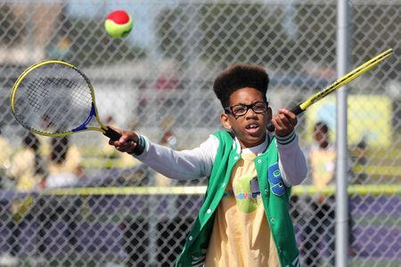 Cameron Campbell, 11, tries to catch a ball at a tennis workshop featuring U.S. Open Champion Sloane Stephens teaching tennis to 400 elementary students in Compton, California, U.S. April 12, 2018. REUTERS/Lucy Nicholson