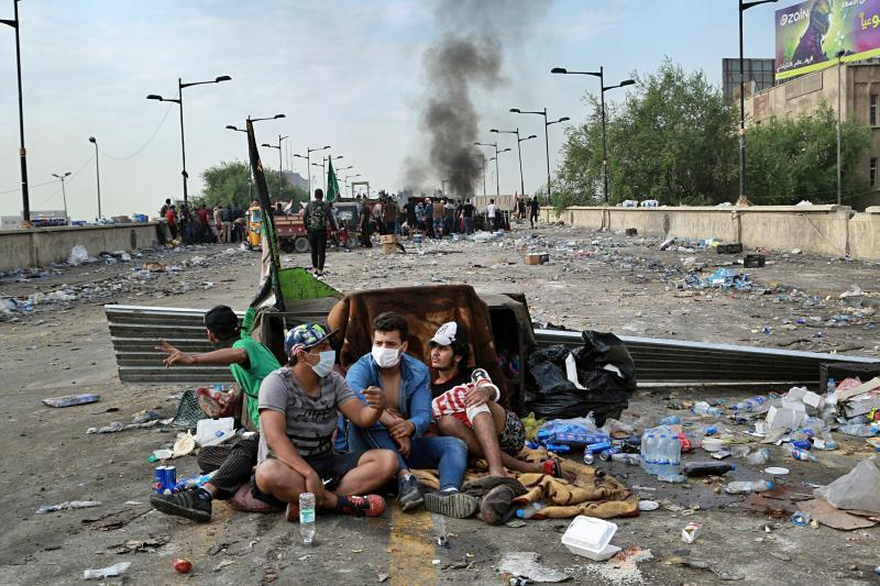Anti-government protesters take cover while Iraqi Security forces close the bridge leading to the Green Zone, during a demonstration in Tahrir square, in Baghdad, Iraq, Sunday, Oct. 27, 2019. (Photo: Hadi Mizban/AP)