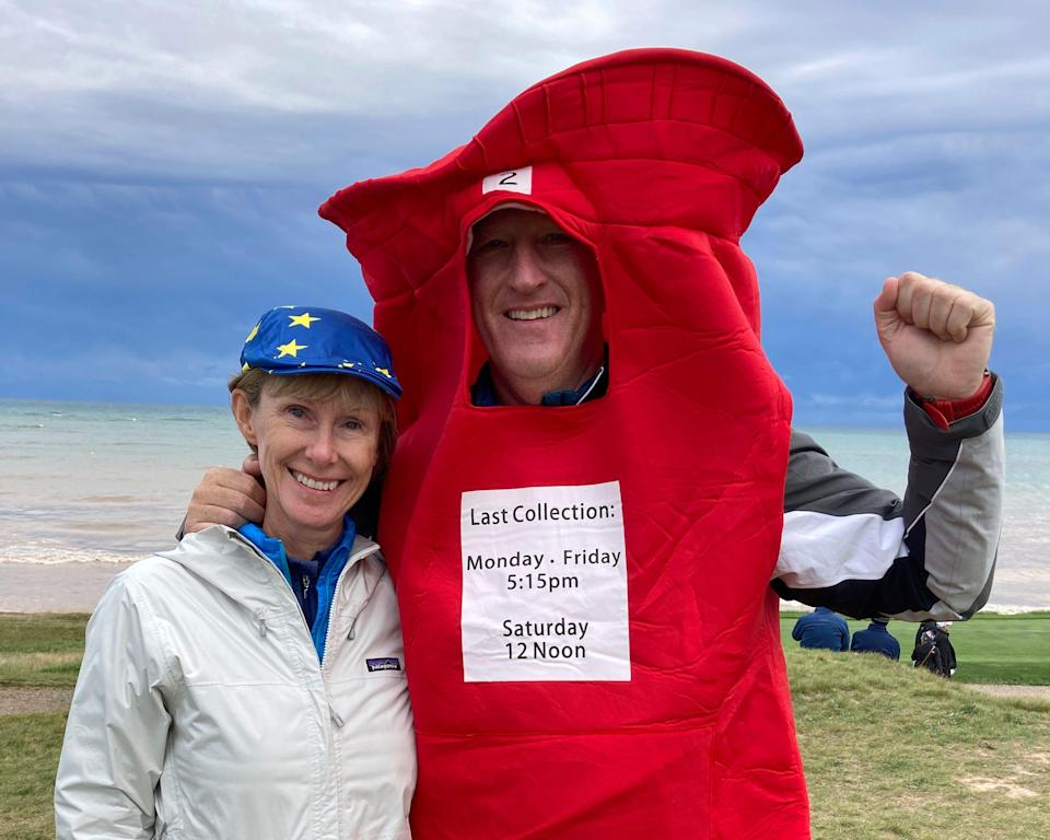 """Gavin Kidd, right, and his wife, Lesley Kidd, left, cheer for Europe during a Ryder Cup golf practice at Whistling Straits on Sept. 23, 2021. Gavin is wearing a mailbox costume to honor European golfer Ian Poulter, who has been nicknamed """"The Postman."""""""
