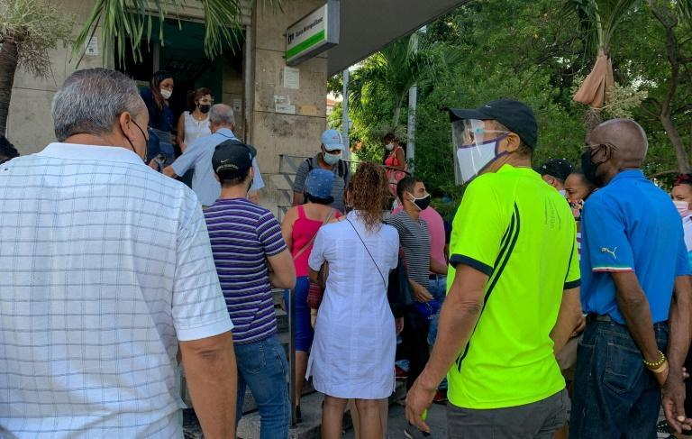 People line up outside a bank branch in Havana on June 11, 2021, to deposit US dollars before the government put into effect a new decree that suspended such deposits in the country's banks