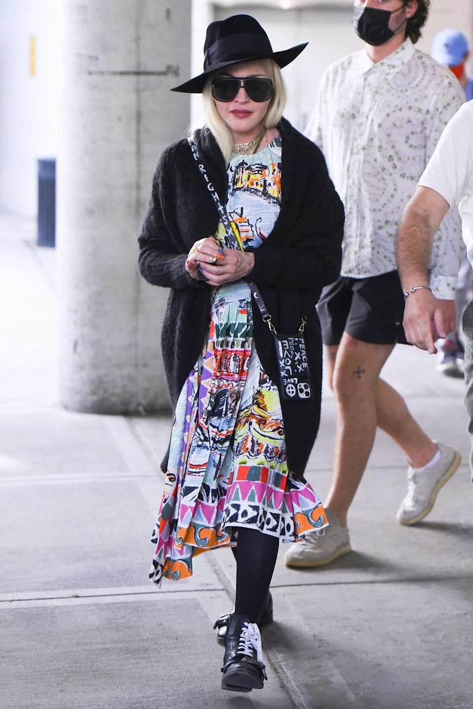 <p>Madonna arrives at JFK Airport in N.Y.C. wearing a colorful dress paired with a black fedora on June 7.</p>